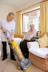 carer helps her elderly pacient by vacuuming her carpet for her