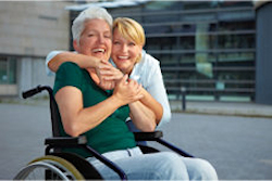 Smiling disabled senior woman in wheelchair with extended care nurse